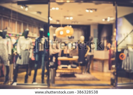 Blurred image of boutique display window with mannequins in fashionable dresses for background. Vintage effect. - stock photo