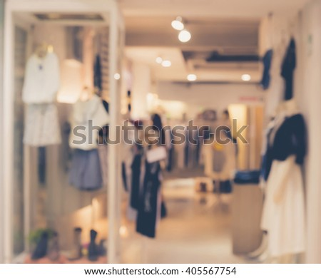 Blurred image of boutique display window with mannequins in fashionable dresses for background. Toned image. - stock photo