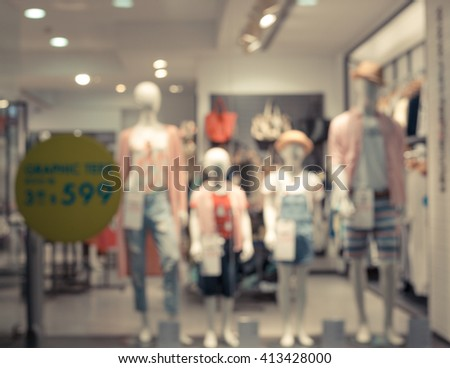 Blurred image of boutique display window with mannequins in fashionable dresses for background.  Toned image. Toned image. - stock photo