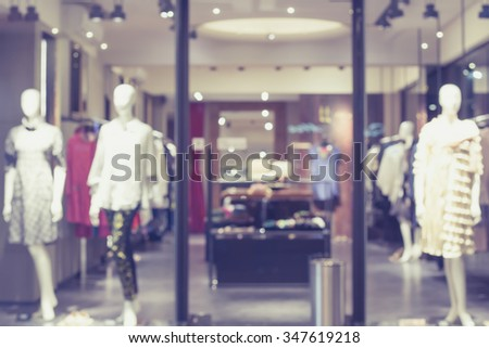Blurred image of boutique window with dressed mannequins. Boutique display window with mannequins in fashionable dresses. Toned image. - stock photo