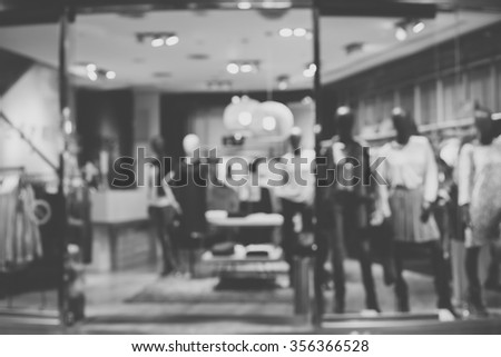 Blurred image of boutique window with dressed mannequins. Boutique display window with mannequins in fashionable dresses. Black and white image. - stock photo