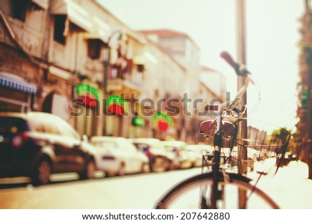 Blurred image of city street with bicycle at sunset with vintage instagram filter effect - stock photo