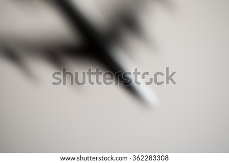 Blurred image of commercial or cargo plane moving fast downwards. Light grey neutral background. Fear of flying
