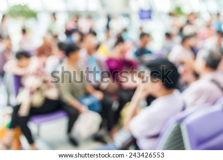 Blurred image of crowd people sitting in departure lounge of terminal Airport.