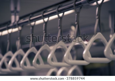 Blurred image of handles for standing passenger inside a subway train. Toned image.