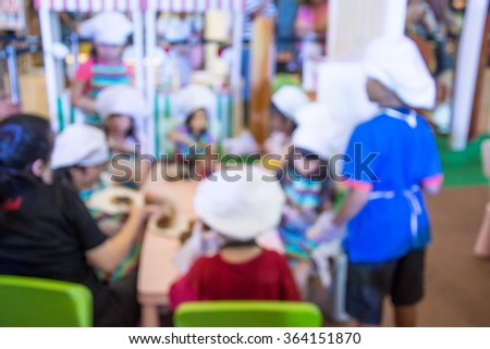 Blurred image of kid playing kitchen toy