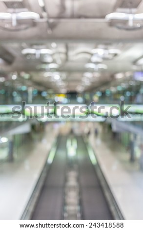 Blurred image of moving modern escalator way in the airport hall. - stock photo