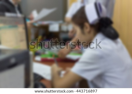 Blurred image of nurse working on documents in hospital