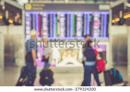 Blurred image of passenger looking to departures display board at airport, Thailand - stock photo