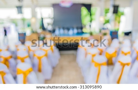 Blurred image of people in auditorium with open space , blur background with bokeh .