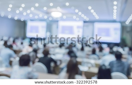 Blurred image of people in auditorium with screen,blue blur color - stock photo