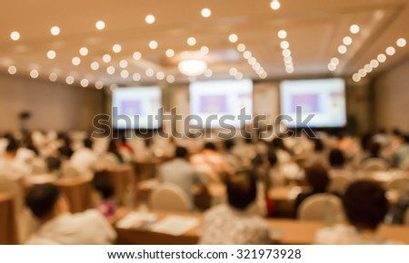 Blurred image of people in hall or auditorium with screen and bokeh light - stock photo
