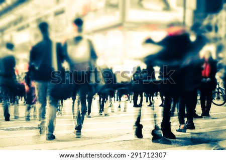 Blurred image of people moving in crowded night city street. Art toning abstract urban background. Hong Kong