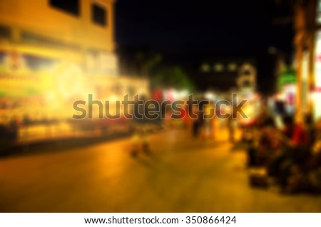 Blurred image of people moving in crowded night city street in Thailand - stock photo