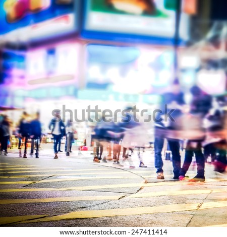 Blurred image of people moving in crowded night city street with sopping malls. Hong Kong. Blur effect - stock photo