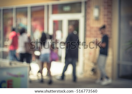Blurred image of people out shopping at pedestrian outdoor courtyards and covered walkways in outlet mall in Houston, Texas, US. Wide range of retailers of designer apparel and jewelry. Vintage filter