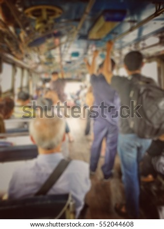 Blurred image of people sitting and standing in public transportation bus in rush hour in the morning