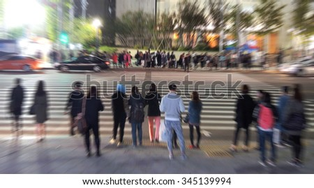 Blurred image of  people waiting to cross the street at night