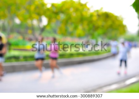 Blurred image of people walking and jogging in the park