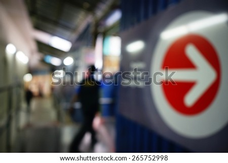 Blurred image of people walking with arrow sign in tunnel  in people moving in crowded night city street with sopping malls. Malaysia. Blur effect and soft focus - stock photo