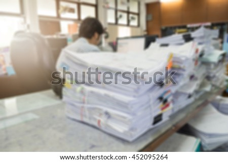 Blurred image of pile of unfinished documents on office desk with working businessman - stock photo
