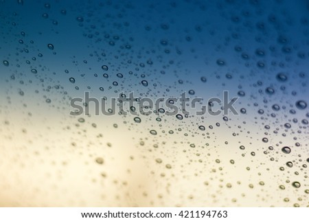 Blurred image of rain drops on windshield and car window.