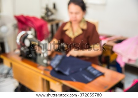 Blurred image of seamstress working on sewing machine - stock photo