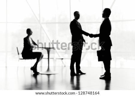 Blurred image of secretary looking at two businessmen handshaking in office