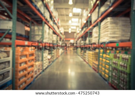 Blurred image of shelves in modern distribution warehouse or storehouse. Defocused background of industrial warehouse interior aisle. inventory, wholesale, logistic and export concept. Vintage filter.