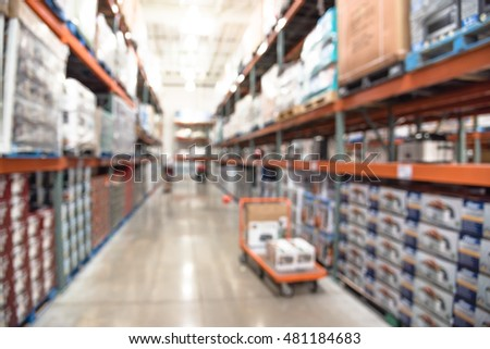 Blurred image of shelves in modern distribution warehouse or storehouse. Defocused background of industrial warehouse interior aisle. inventory, hypermarket, wholesale, logistic and export concept.