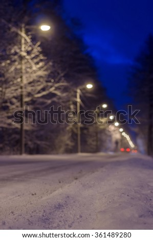 Blurred image of snowy roadside and car rear lights - stock photo