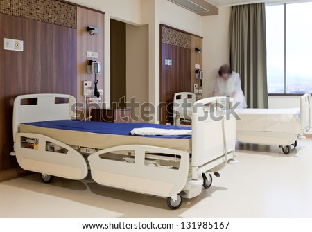 Blurred image of staff member in medical uniform fixing hospital bed