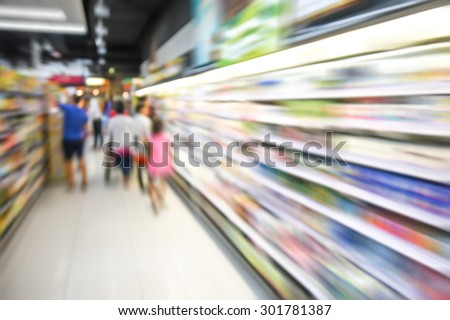 blurred image of supermarket people shopping motion blur- product shelf - business concept