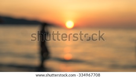 Blurred image of the sunset on the beach. silhouette of a person enjoying the sunset - stock photo