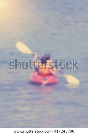 Blurred image of tourist kayaking in the Thai ocean with retro effect - stock photo