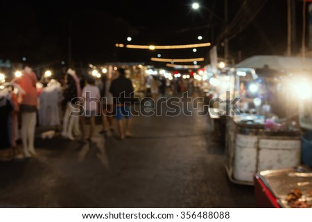 Blurred image of tourists walk in night market