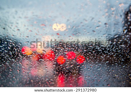 blurred image of traffic view through a car windscreen covered in rain - stock photo
