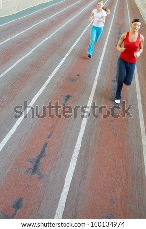 Blurred image of two girls running in gym - stock photo