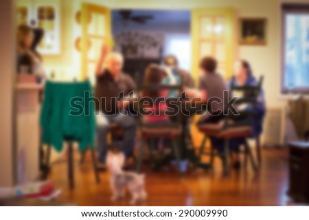 blurred image of Typical American family gathered around kitchen table - stock photo