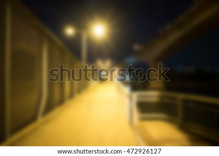 Blurred image of walkway on the bridge at night with the lights dim. lens flare.