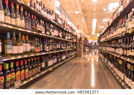 Blurred image of wine shelves display in supermarket. Defocused  Rows of Wine Liquor bottles on the store shelf. Alcoholic beverage abstract background. Alcohol drink market concept.Vintage filter.
