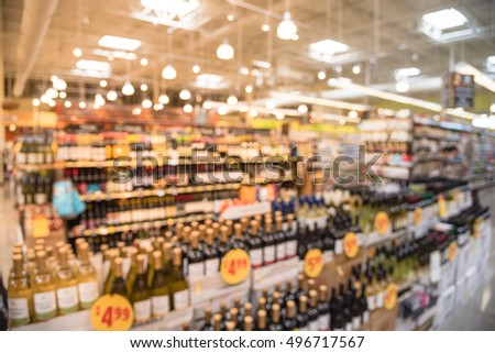 Blurred image of wine shelves with price tags on display in supermarket. Defocused  Rows of Wine Liquor bottles on the store shelf. Alcoholic beverage abstract background. Alcohol drink store concept