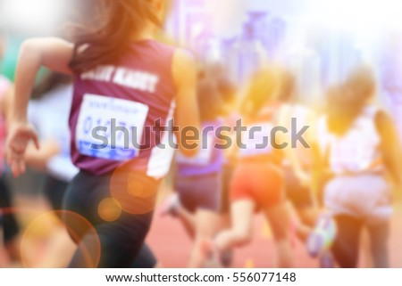 Blurred image of women marathon racing in the city with lans flare.