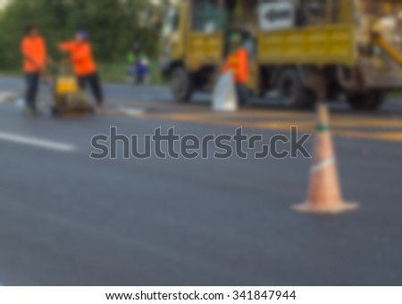 Blurred image of worker on road construction, new asphalt - stock photo