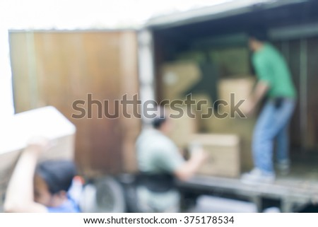 Blurred image of workers lifted carton from the truck, for background uses - stock photo