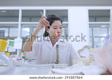 blurred image of Young female researcher in white coat Transplant infections samples in laboratory - stock photo
