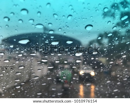 Blurred image, raindrop on the windshield, traffic in the city on a rainy day, car windshield view, colorful bokeh.
