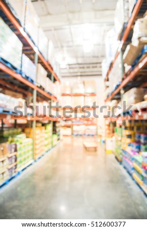 Blurred image row of aisles, bins and shelves from floor to ceiling with flatbed cart in large warehouse. Defocused background industrial distribution storehouse interior aisle, hypermarket, wholesale