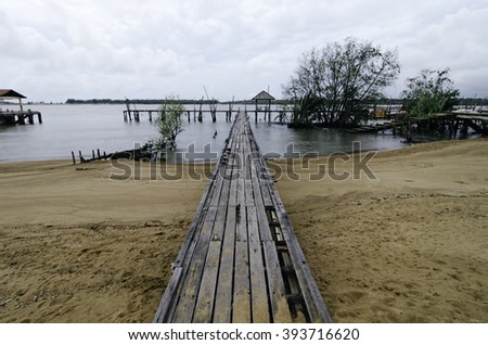 blurred image wooden fisherman jetty with cloudy sky. soft image water due to long exposure shot - stock photo