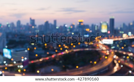 Blurred interchanged road and city downtown background after sunset, abstract background - stock photo